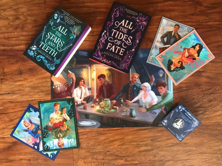 all the stars and teeth paperback, all the tides of fate hardback, character cards x4, character art poster, enamel pin of ship